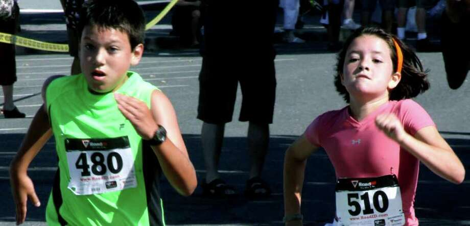 SPECTRUM/More than a bit of pride is at stake Saturday, July 30, 2011 as Matthew Clarke, 11, of New Milford barely holds off Lily Smallidge of South Salem, N.Y. near the finish of New Milford's Village Fair Days 5K. Photo: Walter Kidd