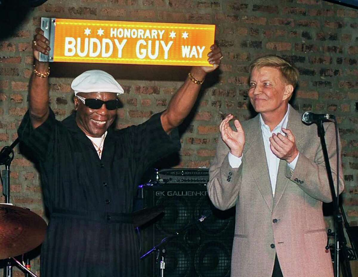 """In this photo taken Sunday, Aug. 7, 2011, Chicago Alderman Robert Fioretti, right, applauds after reading a proclamation from Mayor Rahm Emanuel in honor of Chicago blues legend Buddy Guy, left, who was presented with a street name in his honor at his music club Legends in Chicago. Guy received a copy of the sign as a crowd sang """"Happy Birthday"""" for his 75th birthday which was July 30. (AP Photo/Chicago Sun-Times, Tom Cruze) CHICAGO LOCALS OUT, MAGS OUT"""