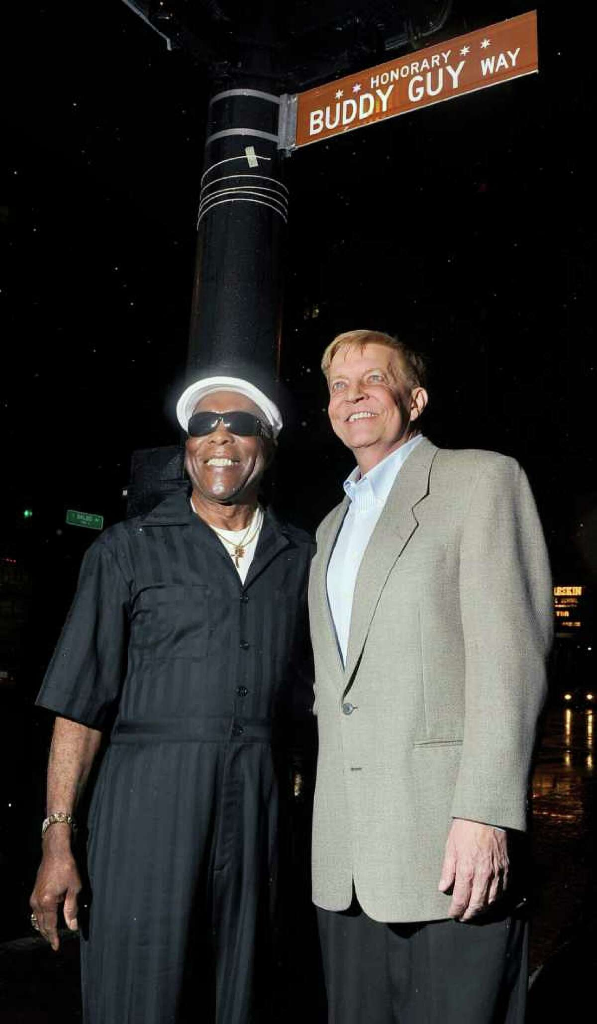 In this photo taken Sunday, Aug. 7, 2011, blues legend Buddy Guy, left, stands under an honorary street sign on his honor with Chicago Alderman Robert Fioretti outside Guy's Legends music club in Chicago. (AP Photo/Chicago Sun-Times, Tom Cruze) CHICAGO LOCALS OUT, MAGS OUT