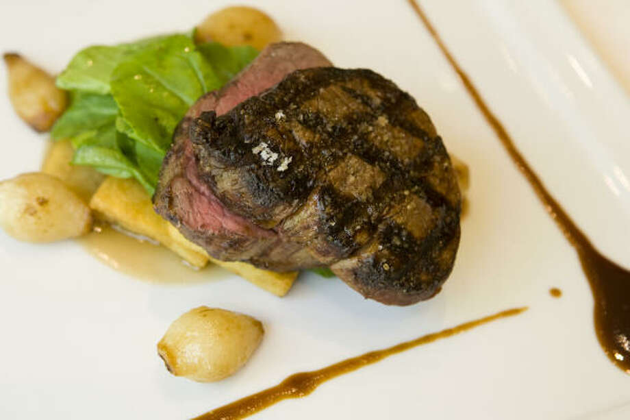 Smoked beef tenderloin piggybacks potato planks and arugula leaves and is accompanied by barely caramelized onions and streaks of bourbon caramel and honeyed sauce. Photo: Steve Campbell, Chronicle