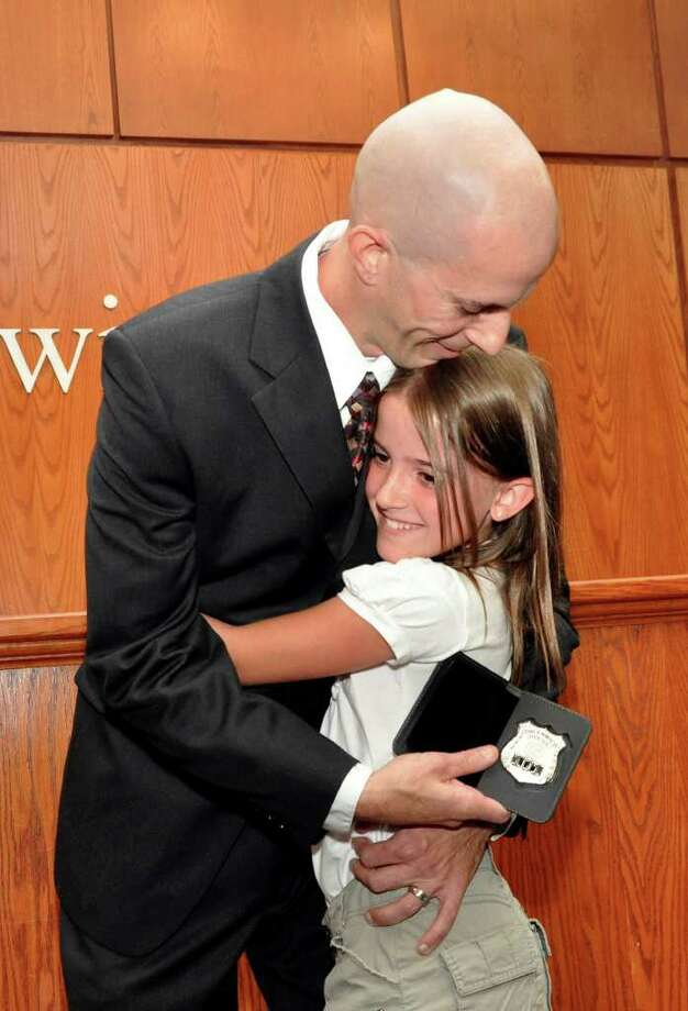 John Tar, newest member of the Greenwich Police Department, hugs his daughter Anni, 10, after receiving his badge during the swearing in ceremony at Greenwich Town Hall on Monday, August, 8, 2011. Photo: Amy Mortensen / Connecticut Post Freelance