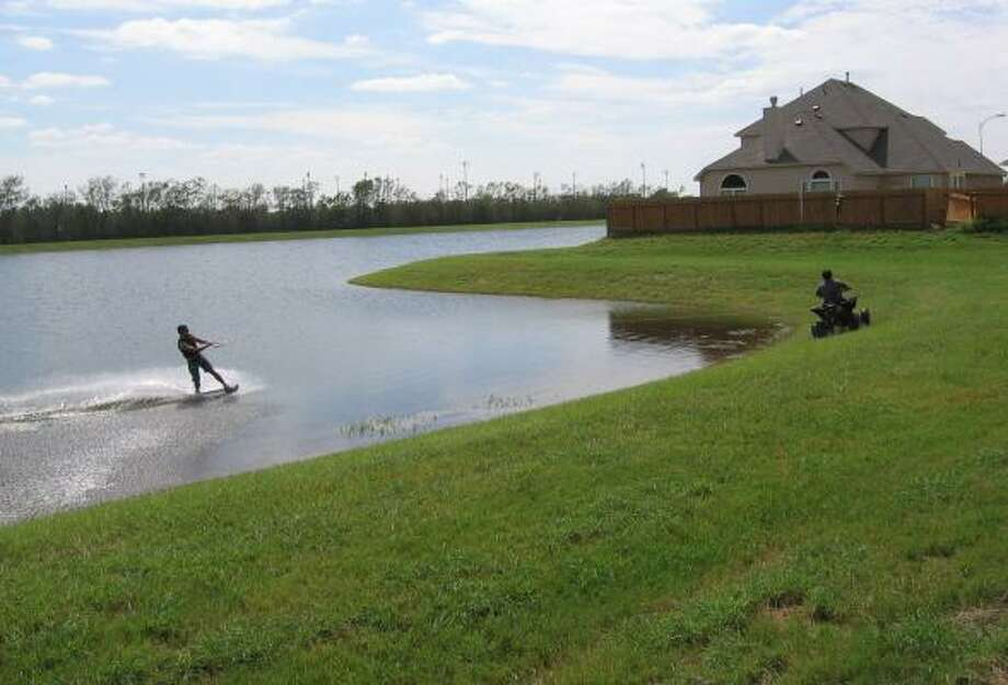 This wakeboarder relieved some post-Ike stress by being pulled around a Pearland retention pond by a four-wheeler. Photo: HELEN OLIN, CHRONICLE