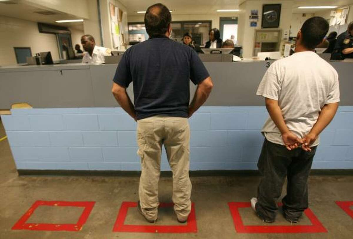 Inmates are interviewed by jailers in the booking office at the Harris County Jail, where officers maintain a database of inmates who tell jailers during booking that they are in the U.S. illegally.