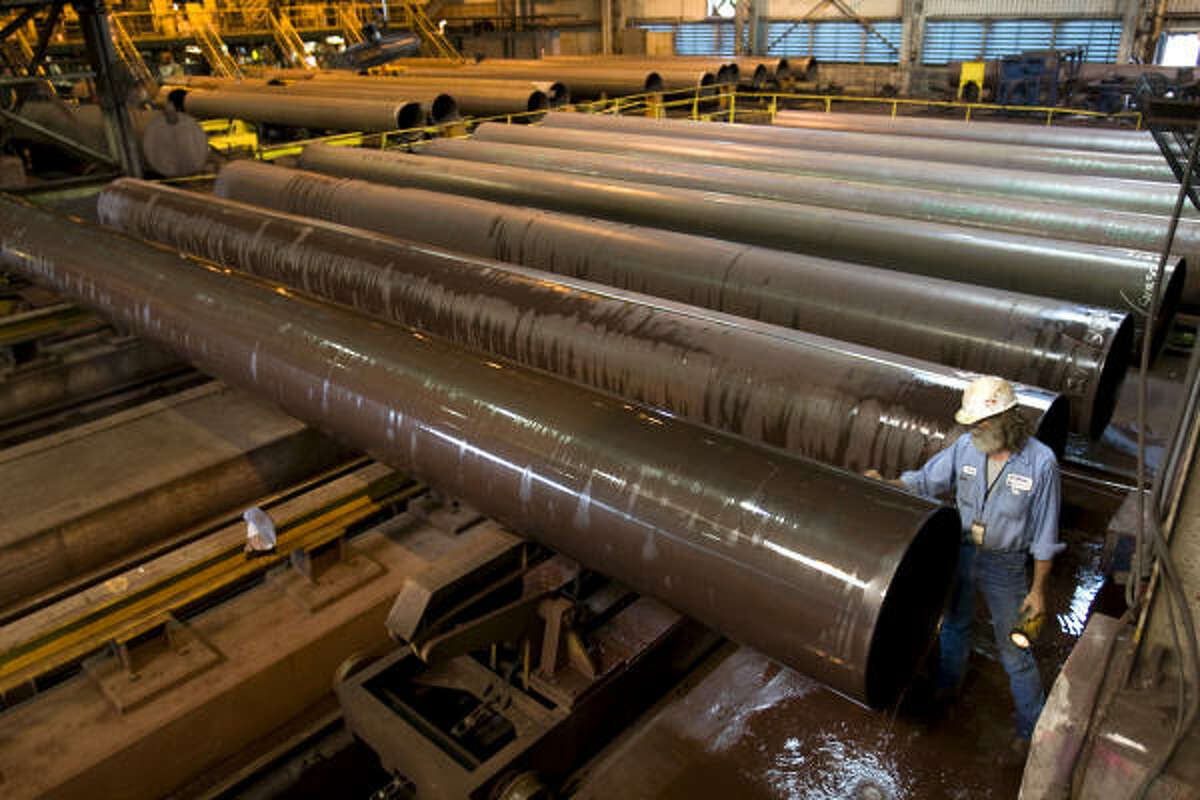 Jeffrey Jacobs marks newly made pipes at JSW Steel USA in Baytown last week. One of the plant's recent projects was cranking out pipe for the Midcontinent Express, a joint venture between Kinder Morgan and Energy Transfer Partners.