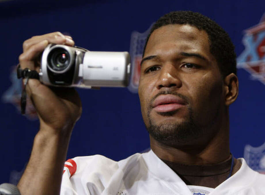 Michael Strahan turns the tables on reporters before answering questions at Tuesday's media day before Super Bowl XLII. Photo: Julie Jacobson, AP
