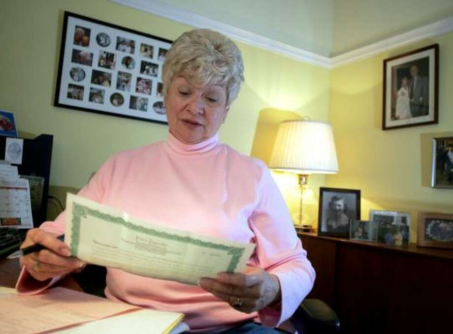 Helen Walker holds the deed to four cemetery plots in Maryland that she is trying to sell as she works in her home office in Indian Trail, N.C. Photo: NELL REDMOND, ASSOCIATED PRESS