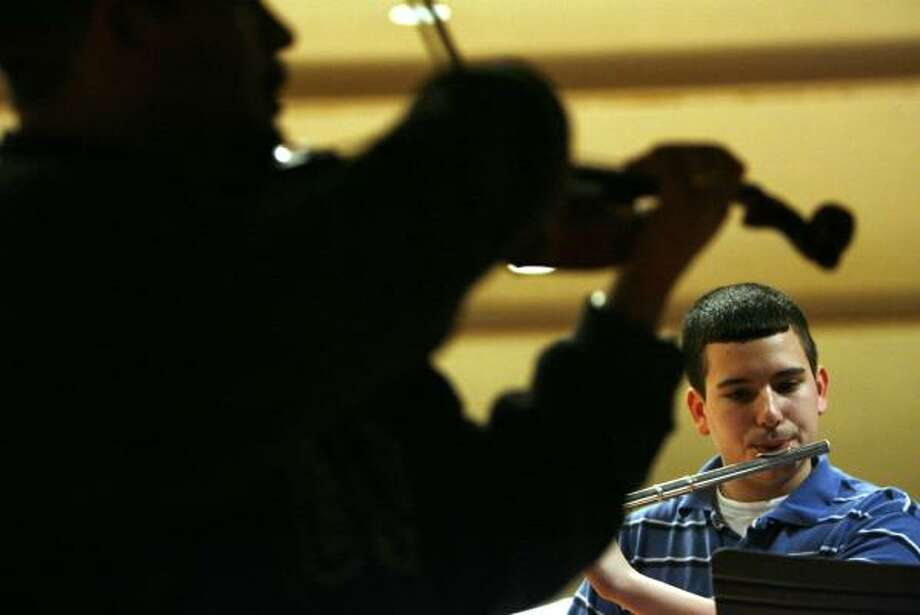 Alex Solis plays flute Friday with teacher Jose Longoria at Patrick Henry Middle School. Photo: JOHNNY HANSON, CHRONICLE