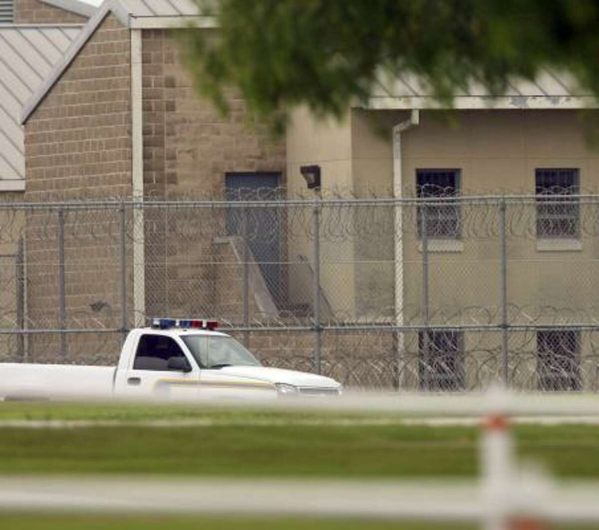 A prison security vehicle patrols the fence line Friday following a riot at the Federal Correctional Institution, near Three Rivers.