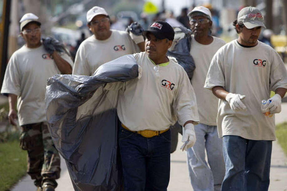 Workers with the Global Restoration Group, a disaster recovery team, many of whom are immigrants from Mexico and Central America, aid in the cleanup of Galveston Island. Photo: Johnny Hanson, Chronicle