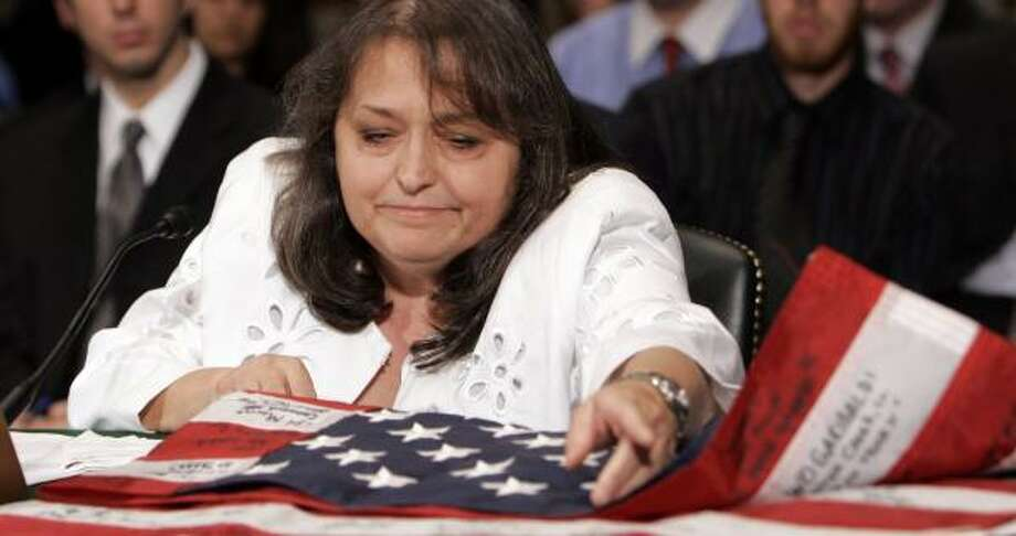 Linda Warren, former employee of KBR, shows the flag she brought back from Iraq during testimony on Capitol Hill on Monday. Warren said many of her colleagues stole numerous items while doing reconstruction work in Iraq. Photo: SUSAN WALSH, ASSOCIATED PRESS