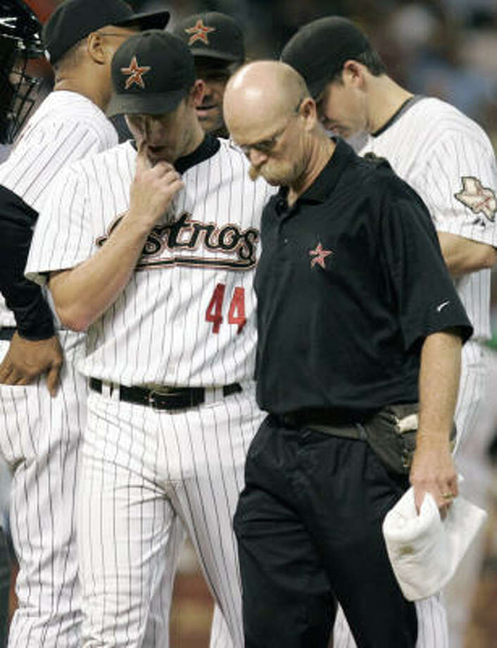 Roy Oswalt (44) walks off the field with trainer Rex Jones after suffering a hip strain against the Dodgers on June 30th. Photo: Pat Sullivan, AP