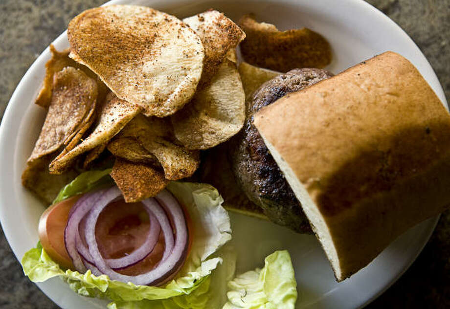 "The Beaver's burger is smallish yet plump and served on a rectangular piece of ""Asian milk bread."" Here is is accompanied by some house-made potato chips. Photo: ERIN TRIEB, FOR THE CHRONICLE"