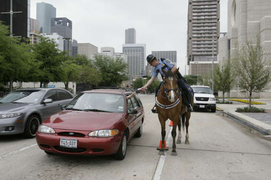 Houston Police Department Mounted Patrol Unit horse Vinson waits patiently as Sgt. Kevin McDaniel checks a motorist's vehicle information. Photo: Julio Cortez, Houston Chronicle