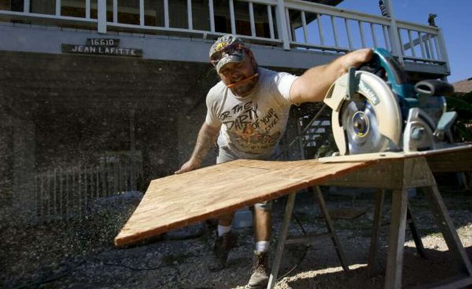 Robert Sawyer cuts plywood Wednesday to board up a home on Jamaica Beach. Photo: JOHNNY HANSON, CHRONICLE