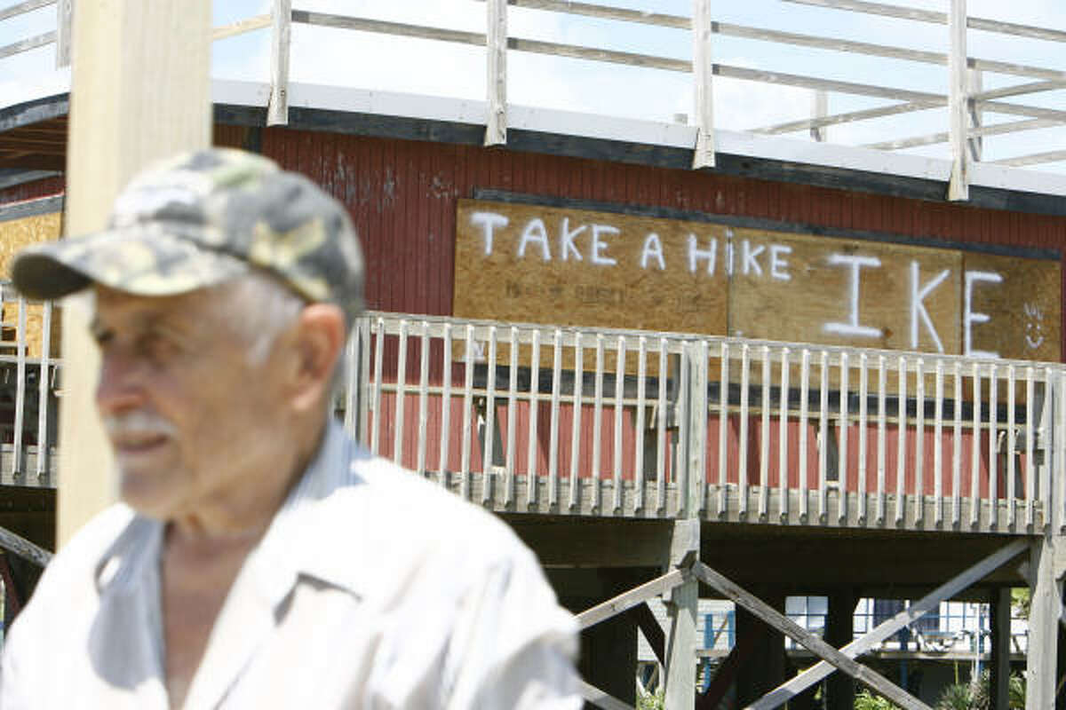 Sam Weido, of Houston, stands near a boarded-up house that has a message for the hurricane in Surfside Beach on Wednesday.