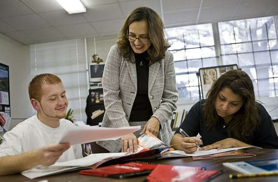 In this 2008 file photo, Sam Houston High seniors Edwin Villarreal, 18, and Ana Alas, 17, put together college applications and scholarship packets with the help of college access coordinator Ivonne Rodriguez. Photo: ERIN TRIEB, FOR THE CHRONICLE