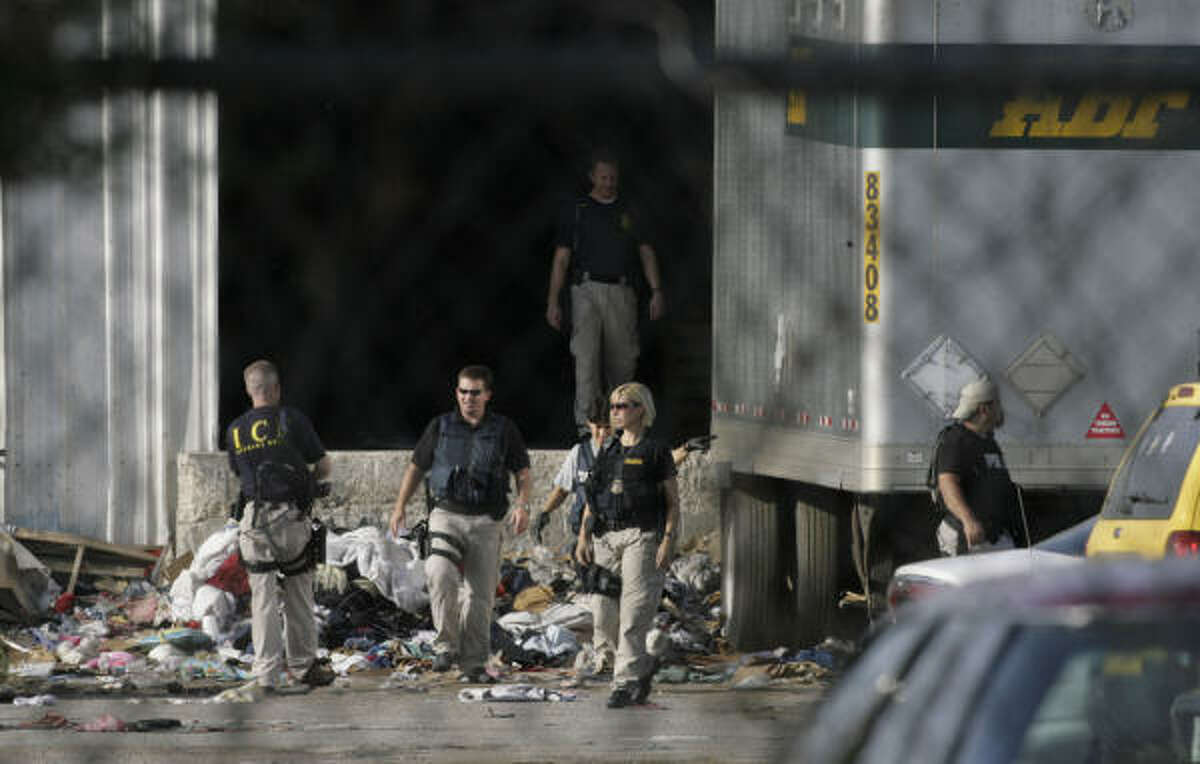 Federal immigration agents search the grounds during an early morning raid at Action Rags USA, near the Houston Ship Channel in east Houston.