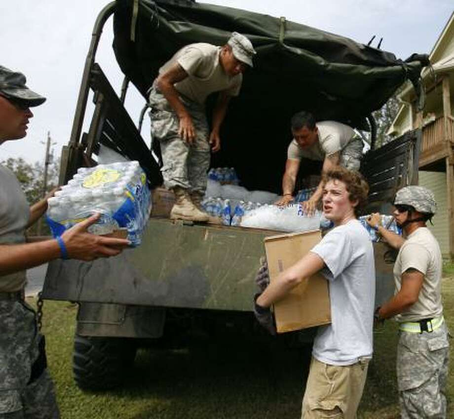 Ryan Wallace picks up food, water and ice from the Texas Army National Guard for his grandmother who lives in San Leon. Photo: Sharon Steinmann, Chronicle