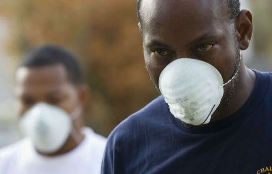 John Levine, right, and his nephew, Anthony Levine, don protective masks as they begin cleaning up in Galveston on Wednesday. Photo: Brett Coomer, Chronicle