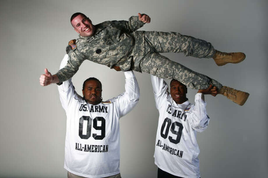 Finalists for the 2009 U.S. Army Player of the Year Award, Jamarkus McFarland, left, and Reuben Randle, right, lend a hand to Army Drill Sergeant of the Year Herb Thompson. Photo: Michael Paulsen, Houston Chronicle
