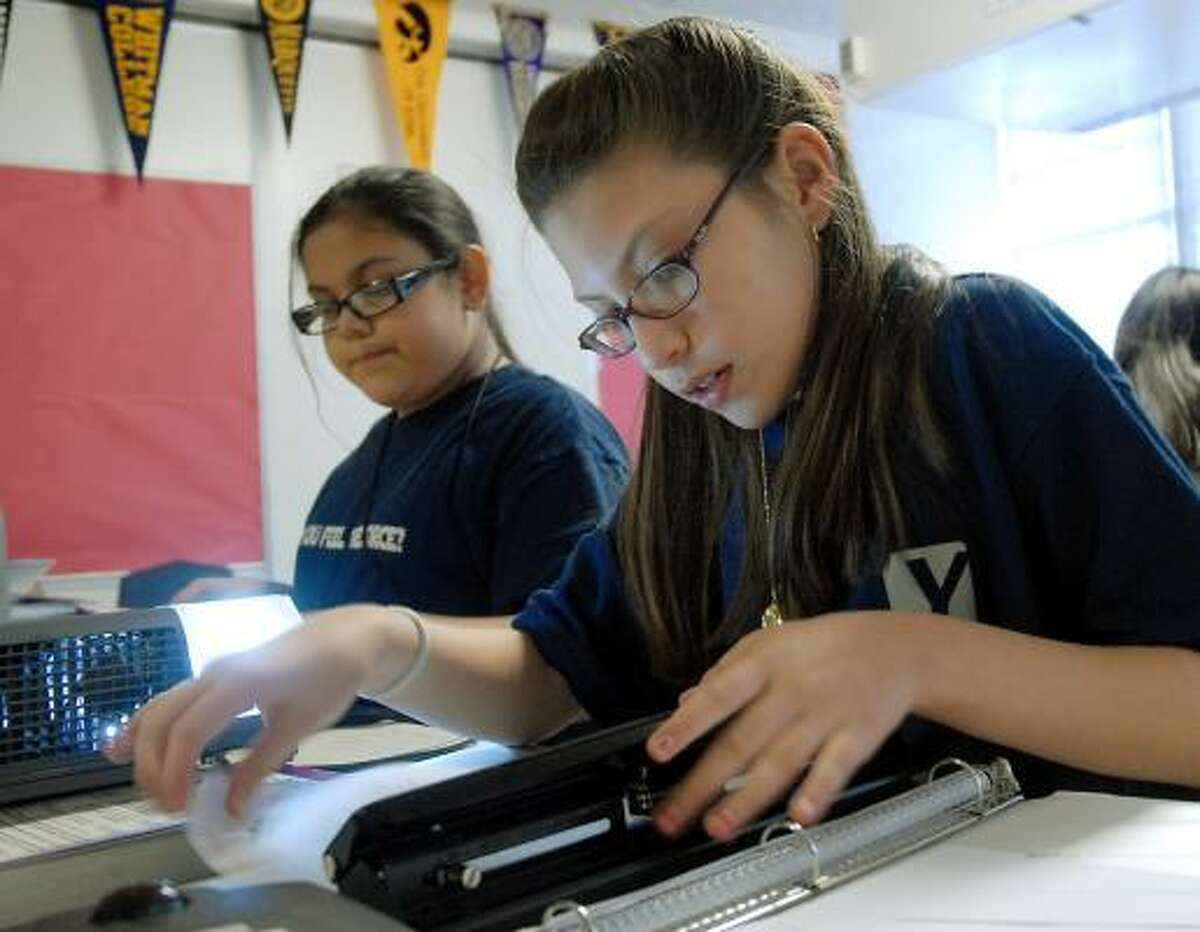 Gloria Ferreira, right, and Sandra Garcia, students at YES Prep's Lee High School campus, work on homework during their study hall period.