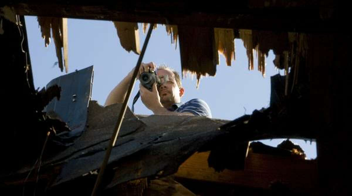 Independent consultant Brian Haden photographs damage to Tom O'Brien's roof.