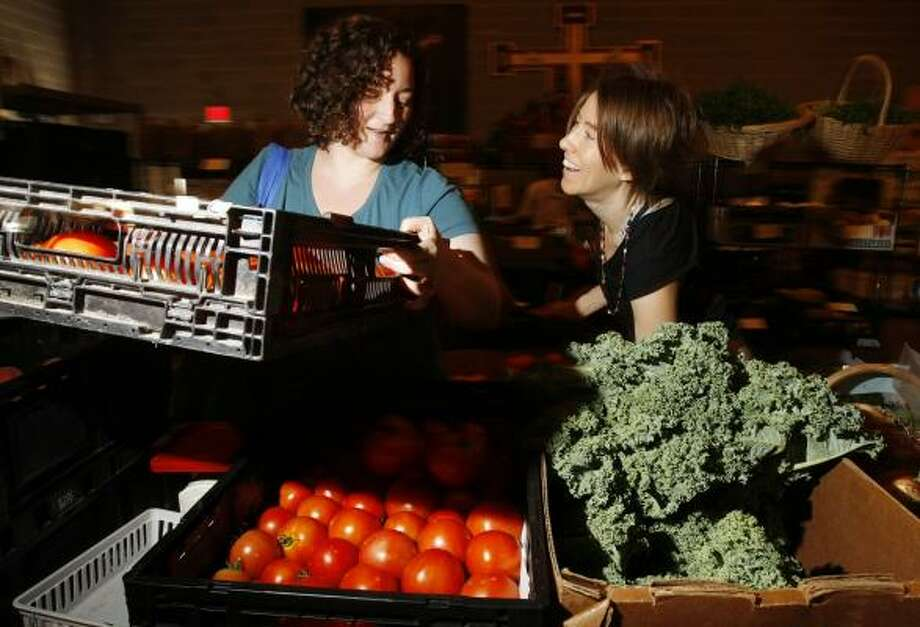 Jennifer Stelly, left, lifts a carton of organically grown tomatoes for Kerry Smith at the Central City Co-Op in Houston. The co-op caters to a growing trend of people exercising ethical consumerism. Photo: KEVIN FUJII, CHRONICLE