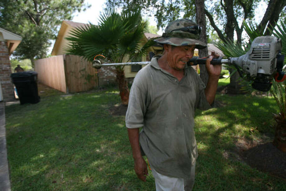 Ismael Hernandez works with a weed trimmer during a landscaping job. Like many businesses, the landscaping operation run by William Perez is being squeezed by high fuel prices. Photo: Mayra Beltran, Houston Chronicle