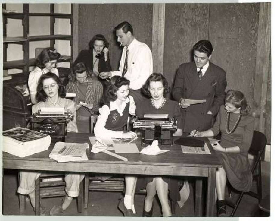 In the early days, the staff of the UH student newspaper The Cougar was divided into day and night crews. Night student Jack Valenti (standing, right) served as news editor and confers with his staff in this 1942 photo. Photo: UNIVERSITY OF HOUSTON, The University Of Houston