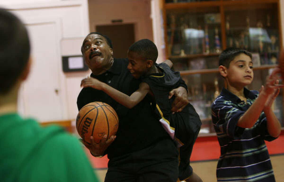 Jerry LeVias, left, director of community outreach at Boys & Girls Harbor in La Porte, clowns around with Marcus Collins, 12, at the gymnasium. LeVias has held the job since February. The Harbor works with Child Protective Services, with an emphasis on volunteer placements.