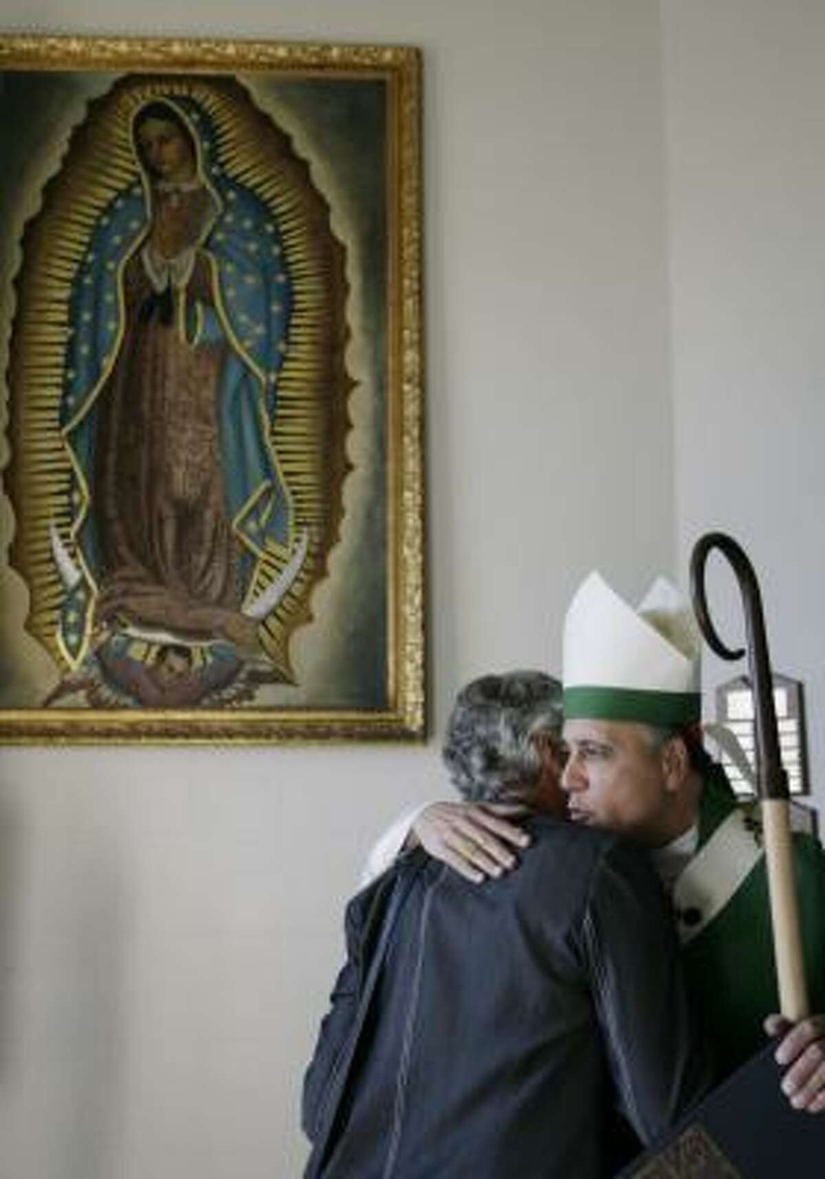Cardinal Daniel DiNardo embraces a parishioner at St. Patrick Church on Sunday.