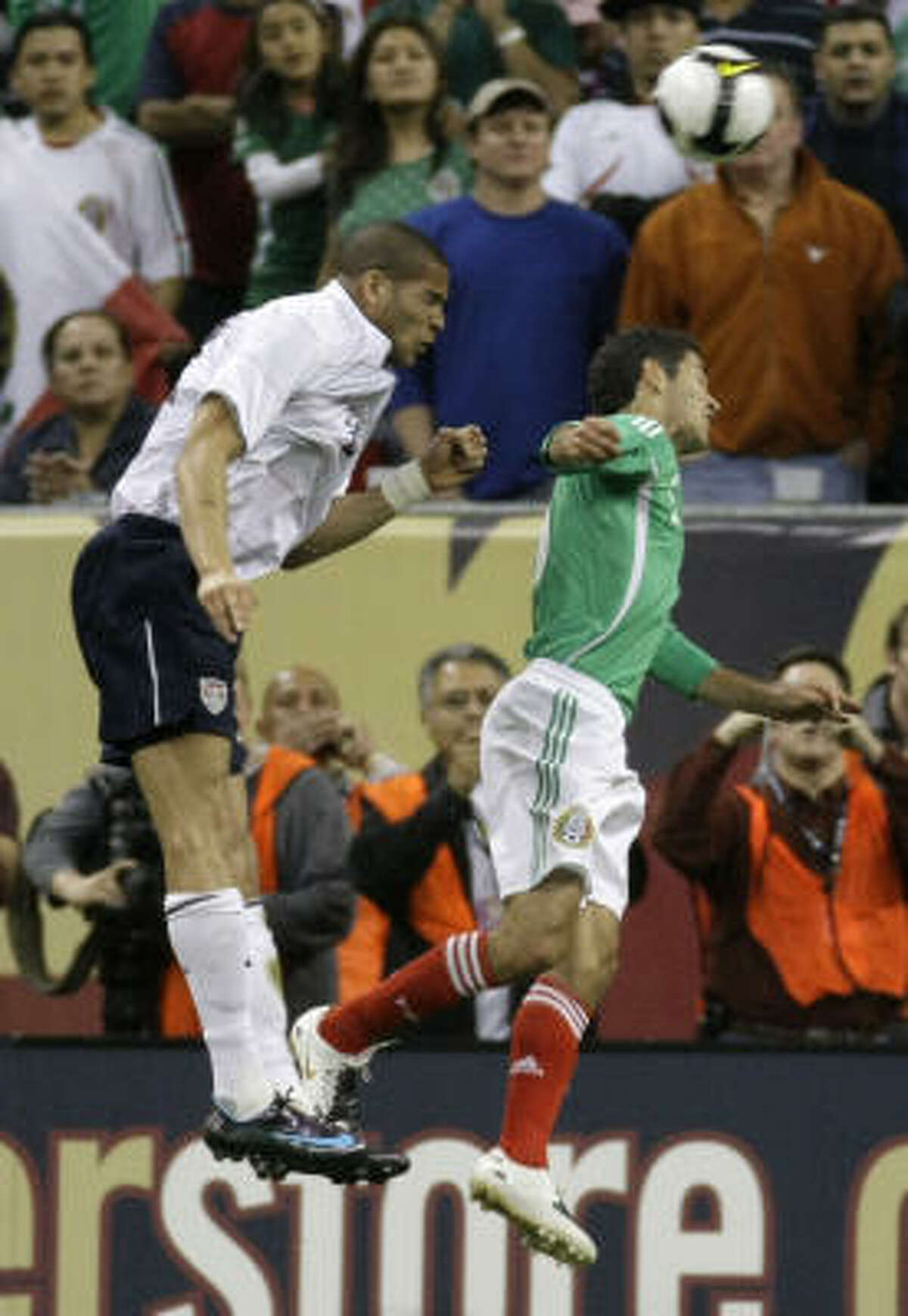 United States' defender Oguchi Onyewu, left, leaps over Mexico defender Israel Castro to head in a goal during the first half.