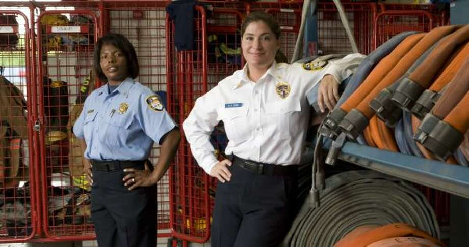 Marion Williams, left, and Alison Stein dealt with more than the ordinary career obstacles at the Houston Fire Department. Photo: BRETT COOMER, CHRONICLE