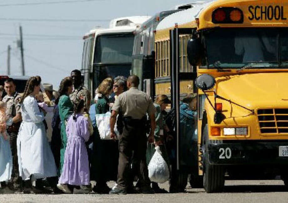 Law enforcement officials assist members of the Fundamentalist Church of Jesus Christ of Later Day Saints onto a school bus in Eldorado on Sunday. The group was relocated to San Angelo. Photo: Tony Gutierrez, AP