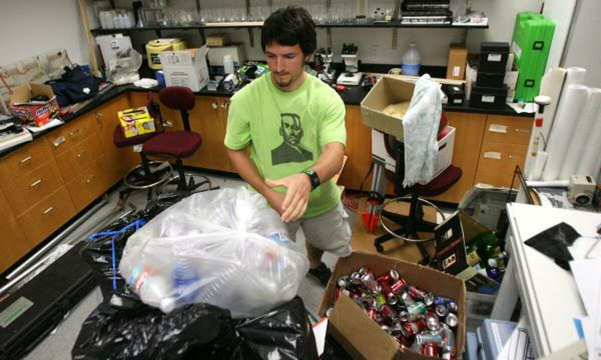 Murray Myers, a student at the University of St. Thomas, sifts through recycled cans and bottles collected last week at the Houston school. Myers runs the campus recycling program and could have graduated in May, but he wants to find his replacement first.