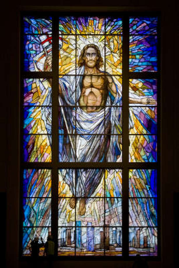 The tiny figures of two workers can barely be seen at bottom left against the massive Resurrection window at the Co-Cathedral of the Sacred Heart in downtown. The 40-foot-tall, 20-foot-wide stained-glass window is on the facade of the cathedral. Photo: Smiley N. Pool, Chronicle