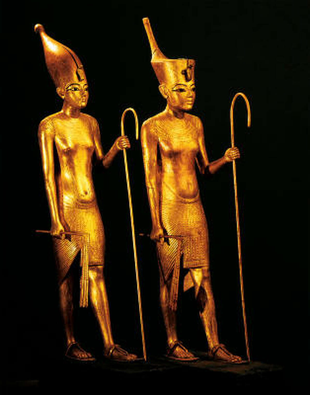 These golden statuettes of King Tut show him wearing the crowns of Upper and Lower Egypt.