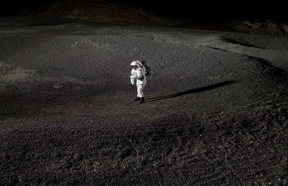 A prototype spacesuit is tested in an artificial crater in the Lunar Yard, a test facility at Johnson Space Center that replicates the moon's surface. Photo: NASA
