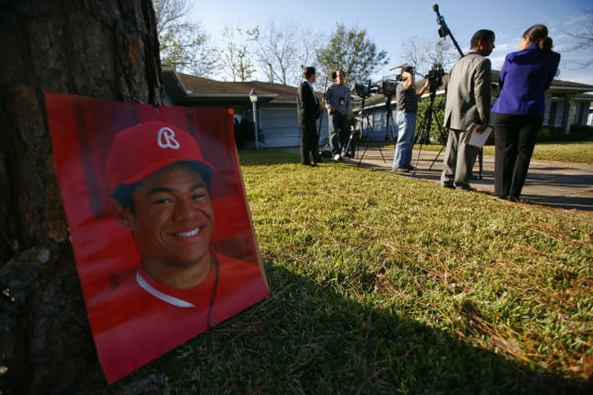 During a news conference on the case Wednesday, a photograph of victim Robert Tolan sits outside his family home, where he was shot.