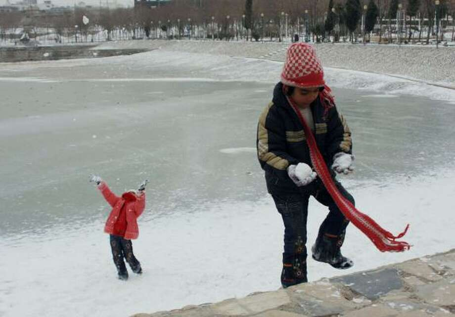 Iraqi girls enjoy playing in snow in Sulaimaniyah, northeast of Baghdad on Friday. About 160 miles away, many residents of Baghdad saw the white stuff for the first time. Photo: YAHYA AHMED, ASSOCIATED PRESS