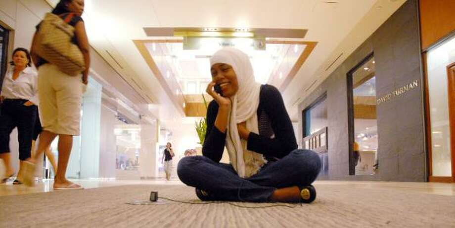 Fatimah Abdulbari chats while charging her cell phone Monday in the Galleria. Photo: DAVE ROSSMAN PHOTOS, FOR THE CHRONICLE