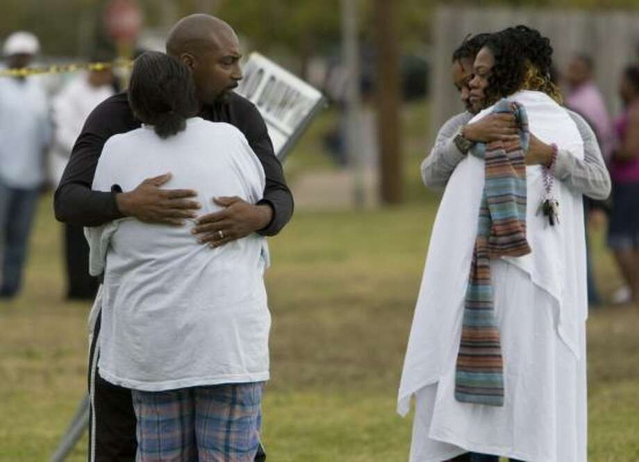 Family members embrace each other after the shooting during a family party in the 7000 block of Pouter early Saturday. Charles Smith killed his wife, Myrle, then shot himself, officers said. Photo: Johnny Hanson, Chronicle