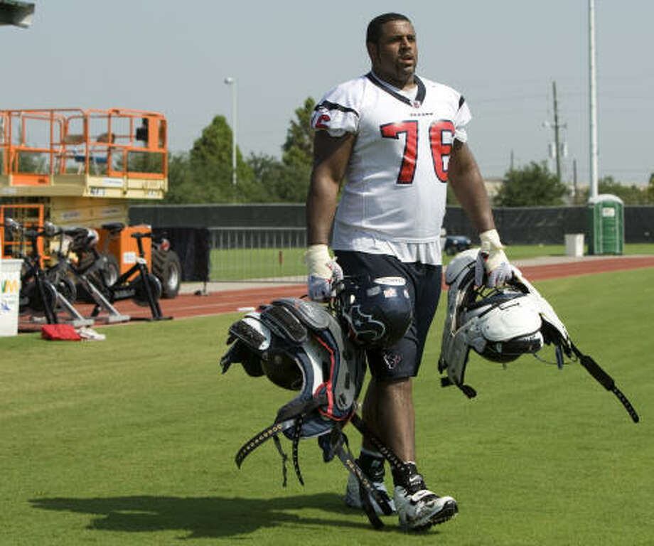 Duane Brown carries a pair of veterans' shoulder pads as he walks off the practice field. Photo: Brett Coomer, Houston Chronicle