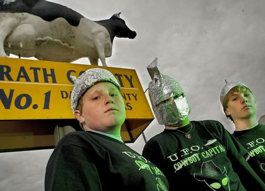 Dakota Jones, Shawn Thompson and Montana Chechick, all 15, show off their tin-foil hats and UFO T-shirts in Stephenville's town square on Friday. Calls and e-mails have flooded the town newspaper since residents reported an unknown object in the sky on Jan. 8. Photo: BRANDON WADE PHOTOS, FOR THE CHRONICLE