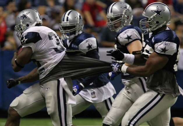 Cowboys running back Lonyae Miller (left) runs for yardage with defenders in pursuit on Monday, Aug. 8, 2011 during training camp at the Alamodome. Photo: John Davenport/jdavenport@express-news.net