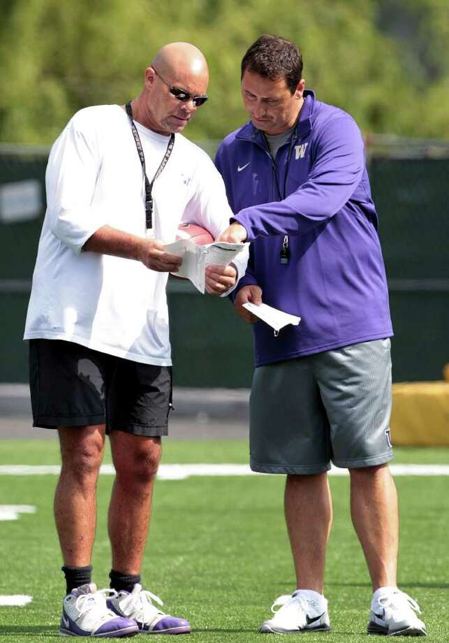 Washington coach Steve Sarkisian, right, goes over practice material with assistant coach Nick Holt during NCAA college football practice Monday, Aug. 8, 2011, in Seattle. Photo: (AP Photo/Elaine Thompson)