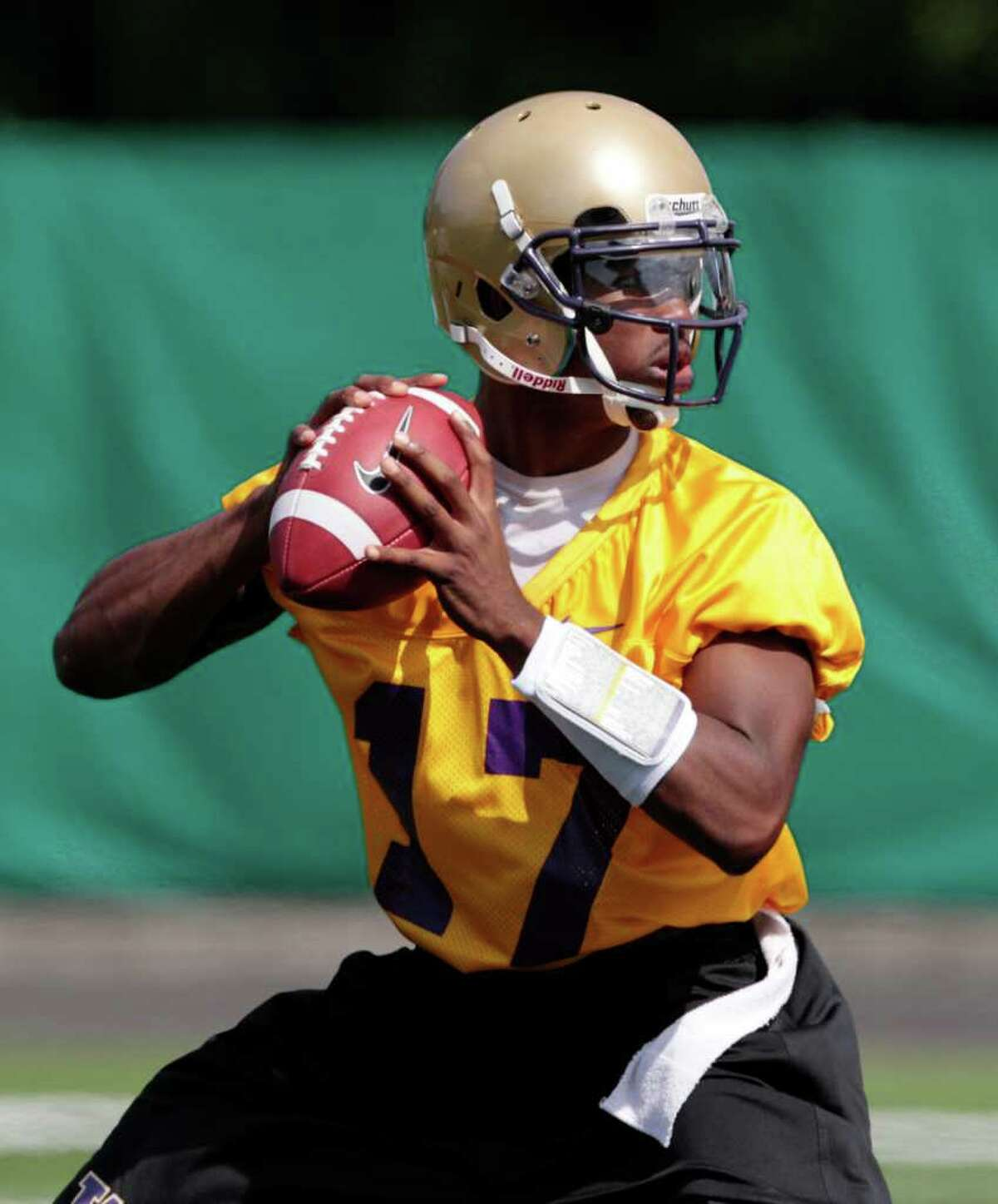 Washington quarterback Keith Price drops back to pass during the NCAA college football team's first practice of the season, Monday, Aug. 8, 2011, in Seattle.