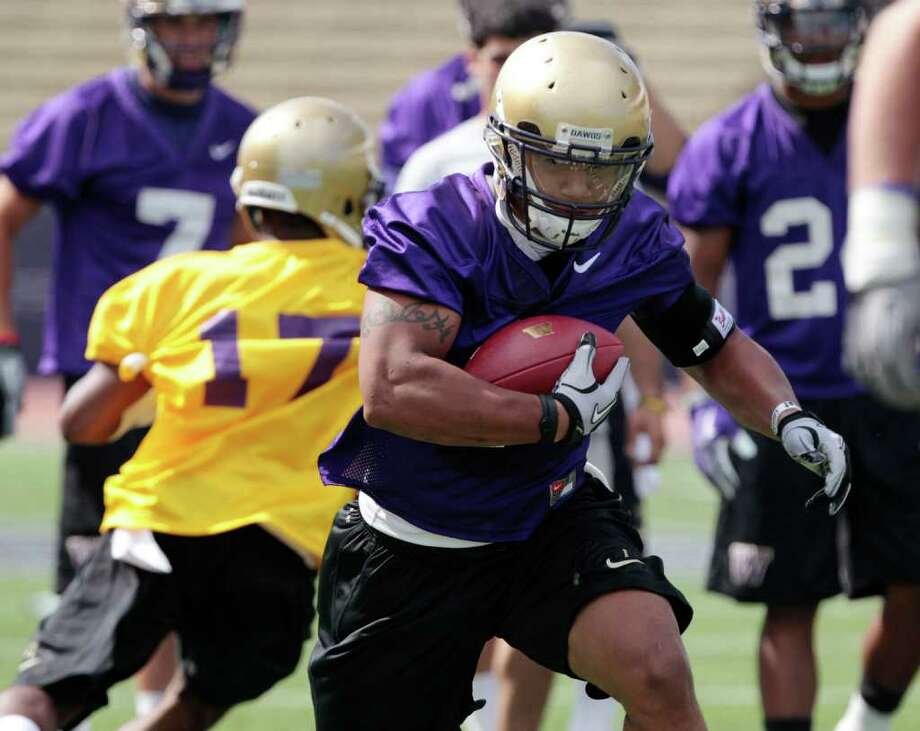 Washington's Chris Polk makes a carry during the NCAA college football team's first practice of the season, Monday, Aug. 8, 2011, in Seattle. (AP Photo/Elaine Thompson) Photo:  (AP Photo/Elaine Thompson)