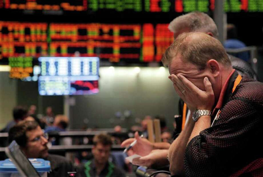 Trader Andrew Stavros reacts after the close of trading in the NASDAQ, 100 Index pit, on the floor of The CME Group Monday, Aug. 8, 2011, in Chicago. Stocks plummeted at the close after anxiety overtook investors on the first trading day since Standard & Poor's downgraded American debt. (AP Photo/M. Spencer Green) Photo: M. Spencer Green, AP / Connecticut Post