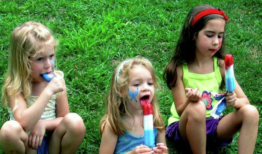 SPECTRUM/Thoroughly engaged in their popsicles are Julia Anderson, 5, left, and her sister, Carolyn, 7, right, and their cousin, Katelyn McGuire, 4, all of New Milford, during the Greater New Milford Chamber of Commerce's 44th annual Village Fair Days on the Village Green in New Milford, July 29, 2011. Nearby and also enjoying a cold treat on a hot summer's day was Katelyn's little brother, Brennan, 2. Photo: Norm Cummings